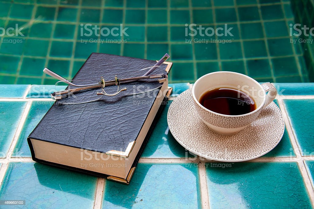 Coffee and book at the pool side royalty-free stock photo