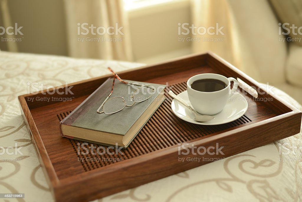 Coffee and book by bedside with reading glasses royalty-free stock photo