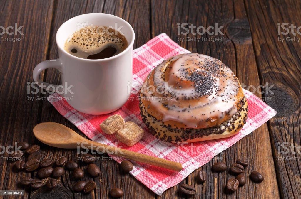 Cup of coffee and fresh sweet bun with poppy seeds on dark wooden...