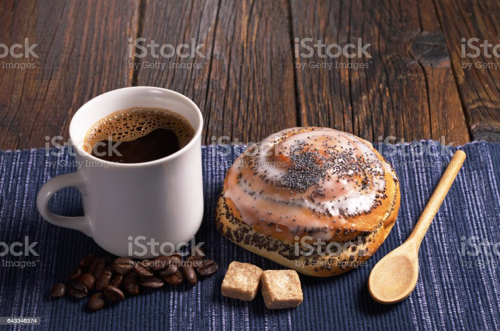 Cup of coffee and delicious bun with poppy seeds on rustic wooden...