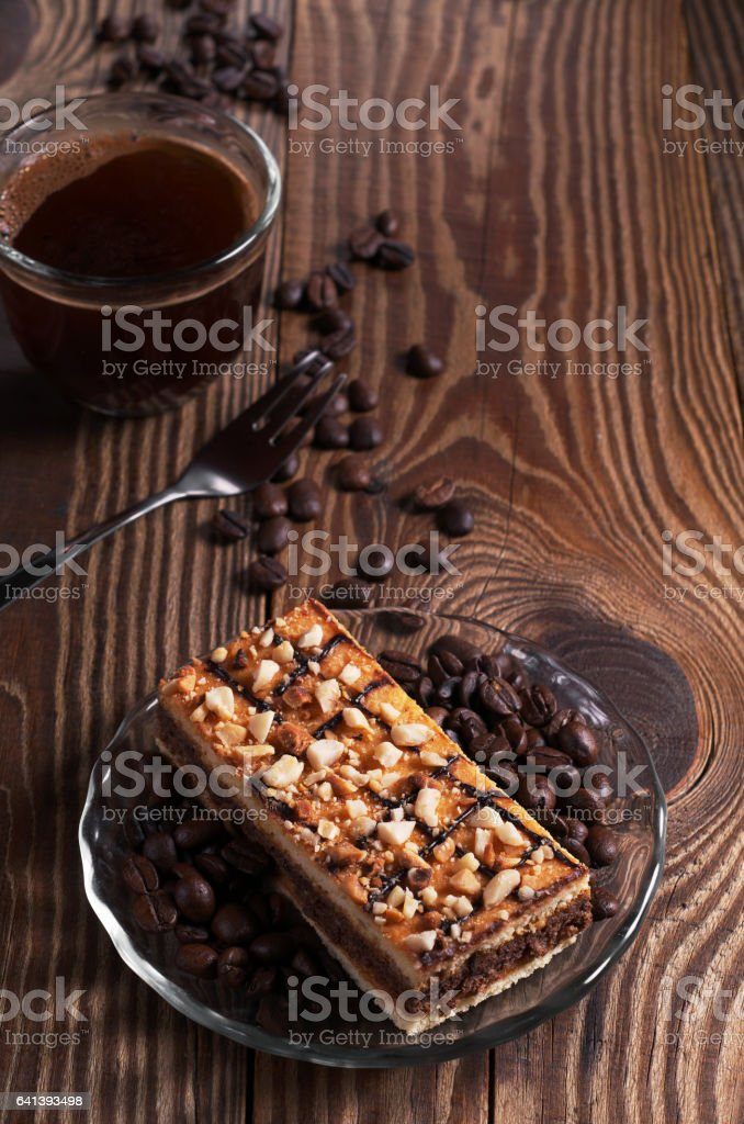Cup of hot coffee and delicious caramel cake with nuts on old wooden...