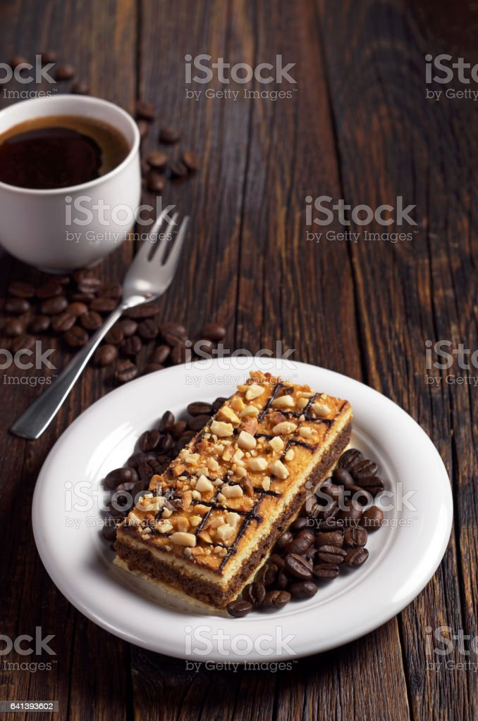Cup of hot coffee and sweet caramel cake with nuts on dark wooden...