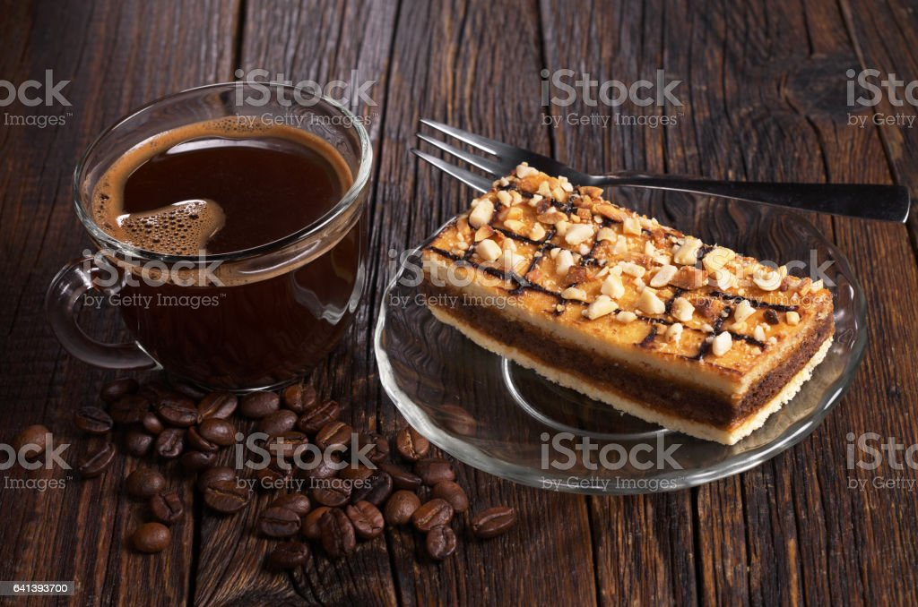 Cup of hot coffee and sweet caramel cake with nuts on old wooden table