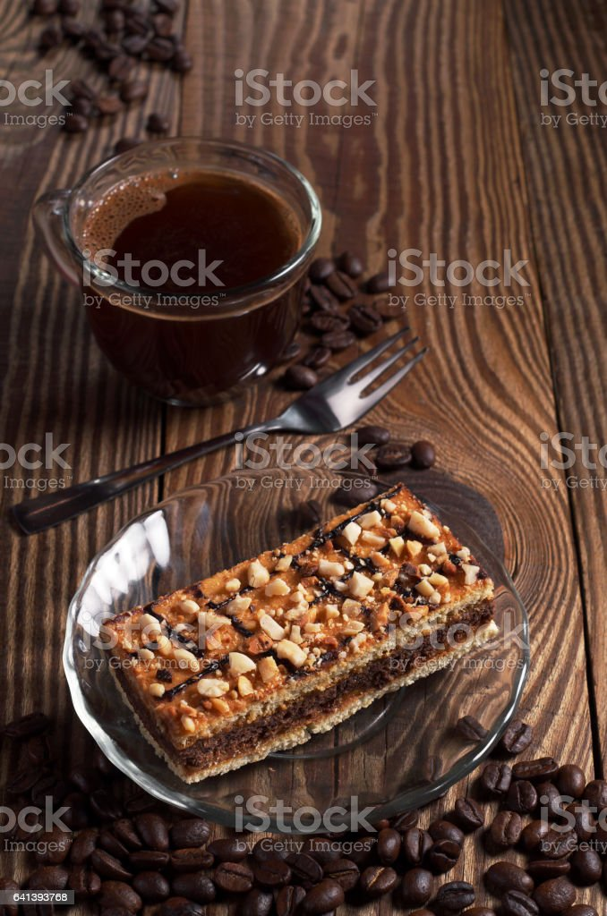 Cup of hot coffee and tasty caramel cake with nuts on old wooden table