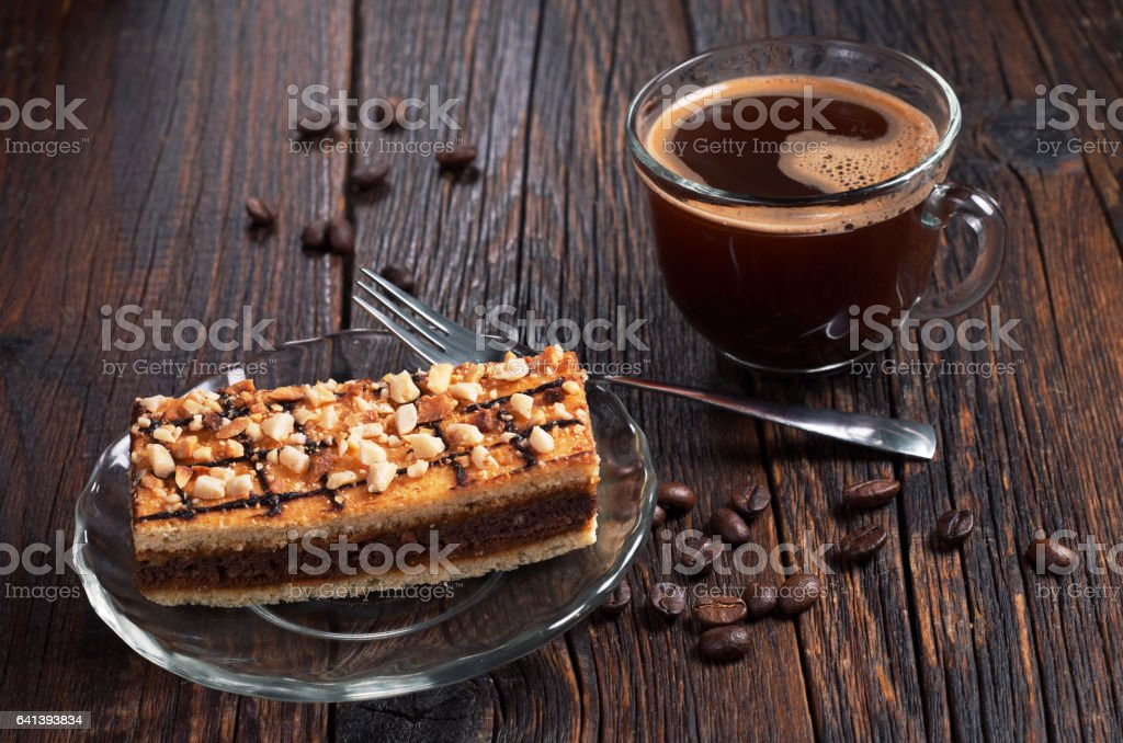 Cup of hot coffee and caramel cake with nuts on old wooden table