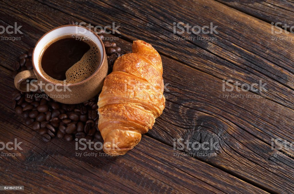Cup of hot coffee and croissant on dark wooden table. Space for text