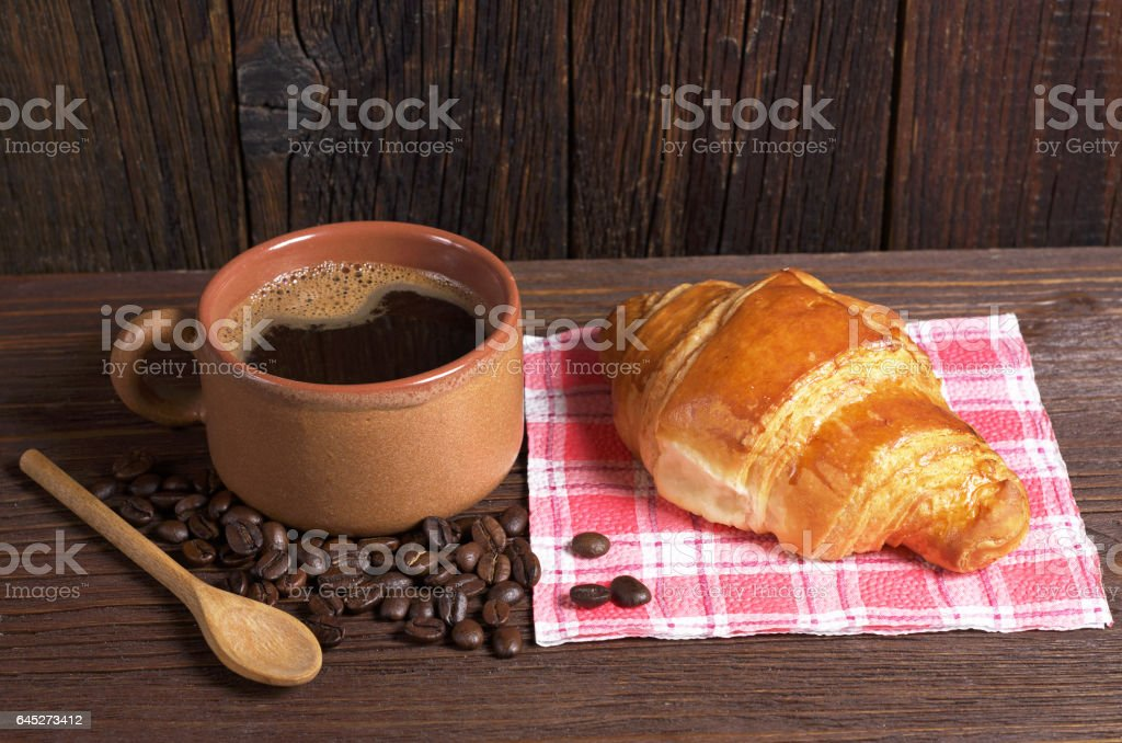 Cup of hot coffee and fresh croissant on dark wooden table