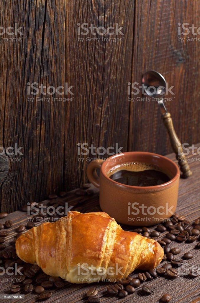 Cup of hot coffee and fresh croissant on old wooden table