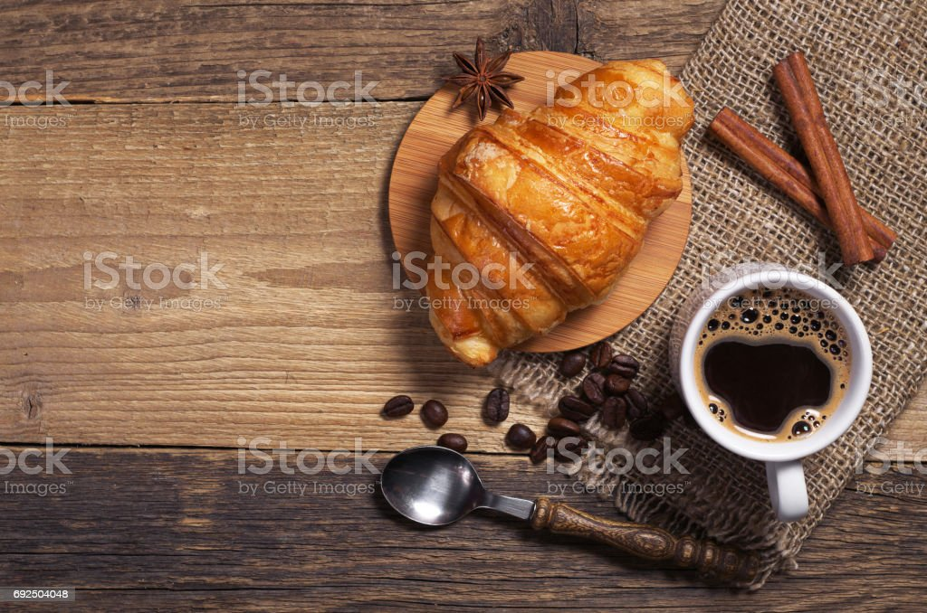 Cup of hot coffee and fresh croissant on old wooden table, top view