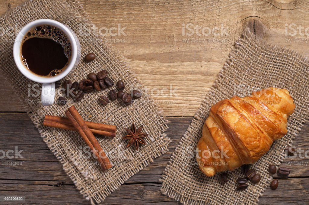 Cup of hot coffee and fresh croissant for breakfast on old wooden...
