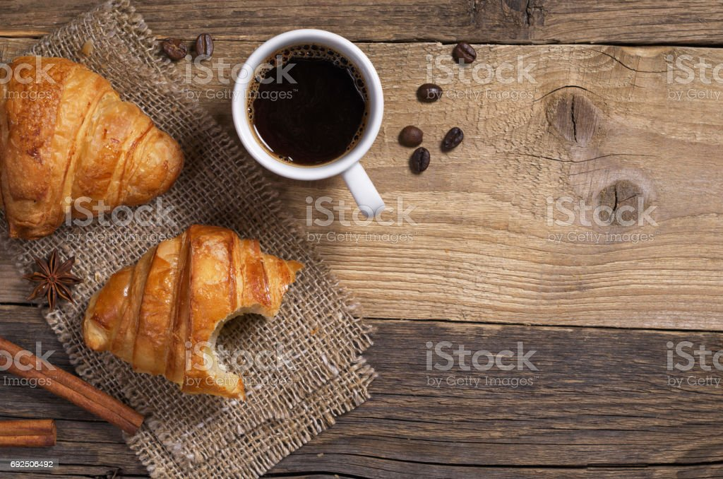 Top view of coffee and fresh croissant for breakfast on old wooden...