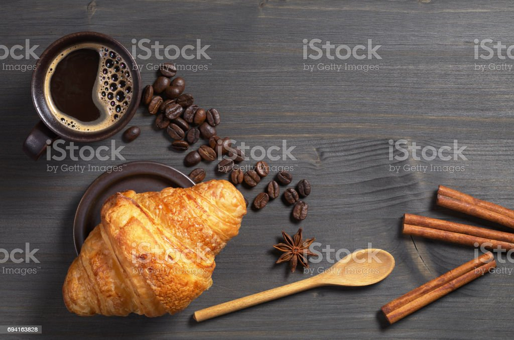 Cup of hot coffee and fresh croissant on dark wooden table, top view