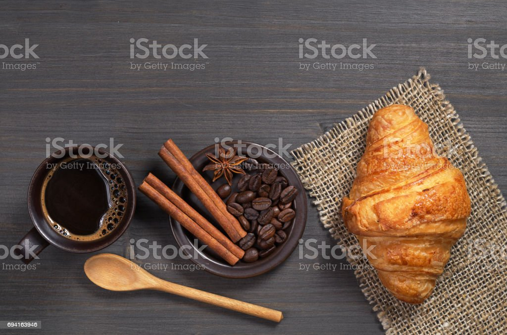 Top view of coffee and fresh croissant on dark wooden table