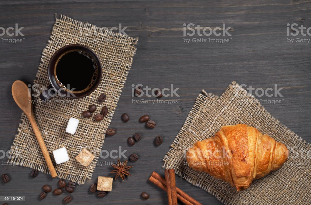 Cup of hot coffee and fresh croissant for breakfast on dark wooden...