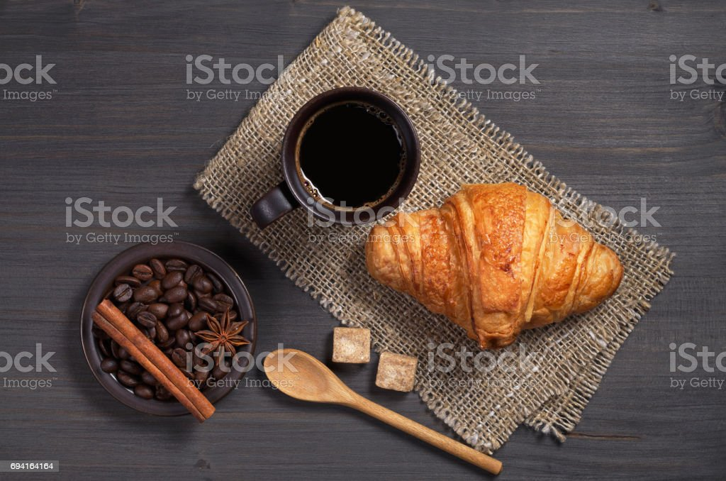 Top view of coffee and fresh croissant for breakfast on dark wooden...