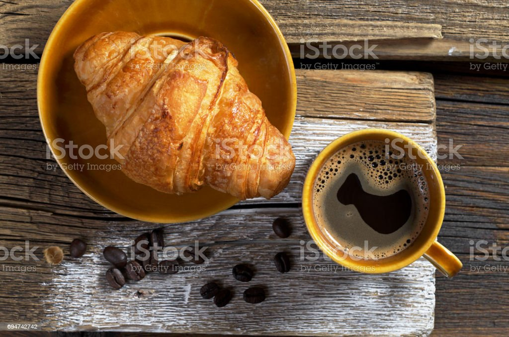 Top view of coffee and fresh croissant on old wooden background, top...