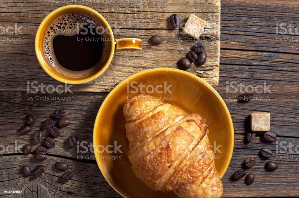 Cup of hot coffee and fresh croissant on old wooden background, top...