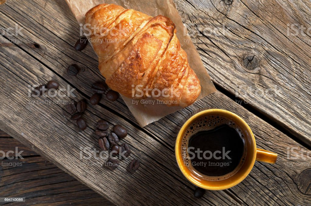 Cup of hot coffee and croissant on old wooden background, top view