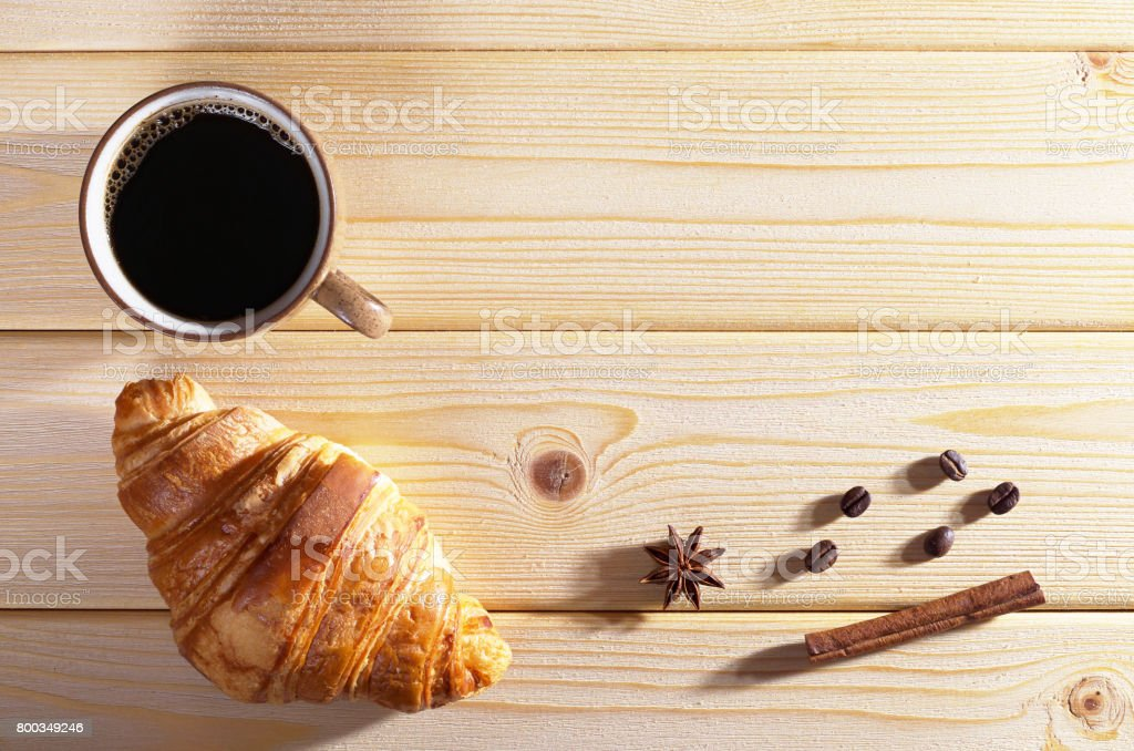 Cup of hot coffee and fresh croissant on wooden table, top view. Low...