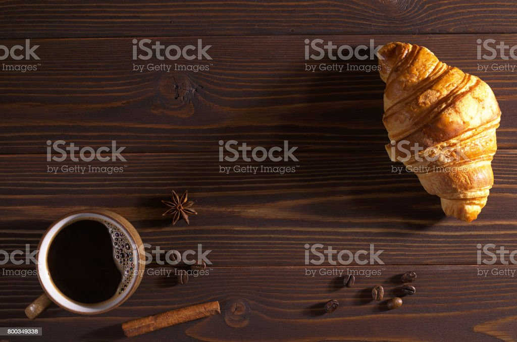 Cup of hot coffee and croissant on dark wooden background, top view....