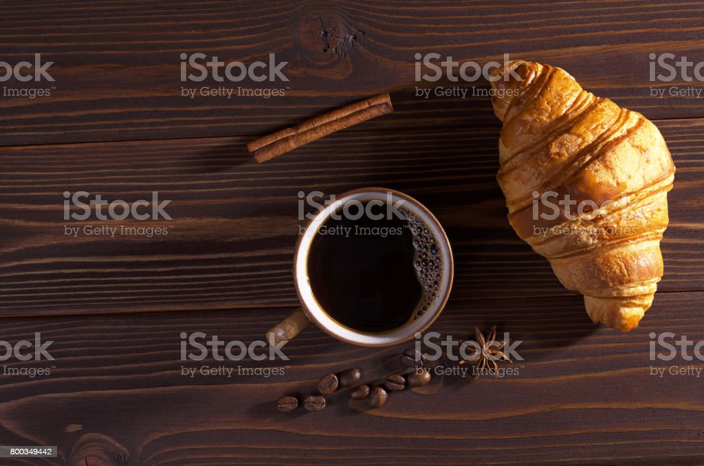 Cup of hot coffee and fresh croissant on dark wooden table, top view....