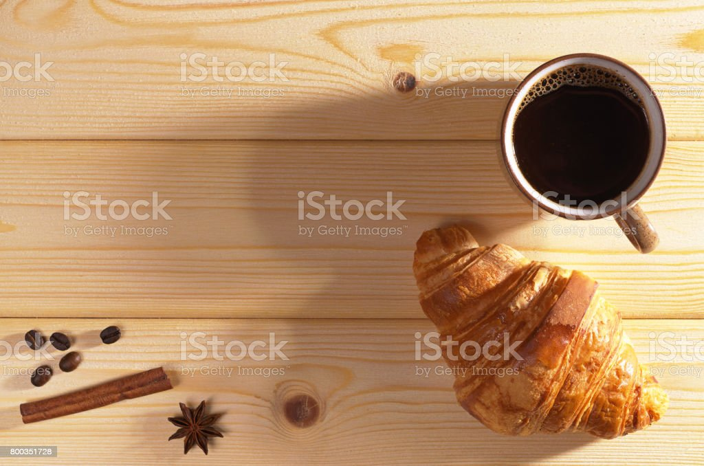 Cup of hot coffee and croissant on wooden background, top view. Lower...