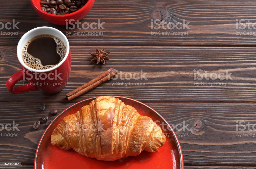 Cup of hot coffee and croissant on dark wooden background. Space for...