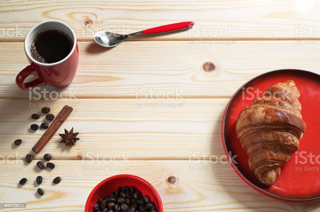 Cup of hot coffee and fresh croissant for breakfast on wooden table....