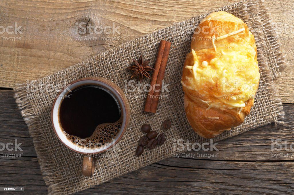 Cup of hot coffee and croissant with cheese for breakfast on old...