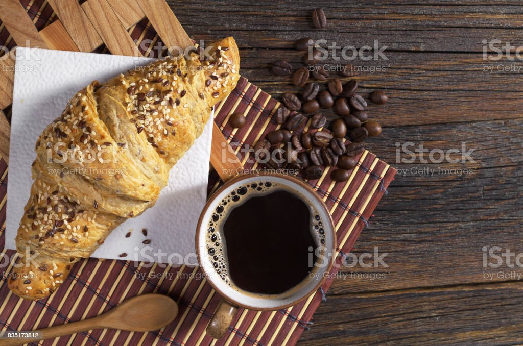 Cup of hot coffee and croissant with sesame seeds for breakfast on...