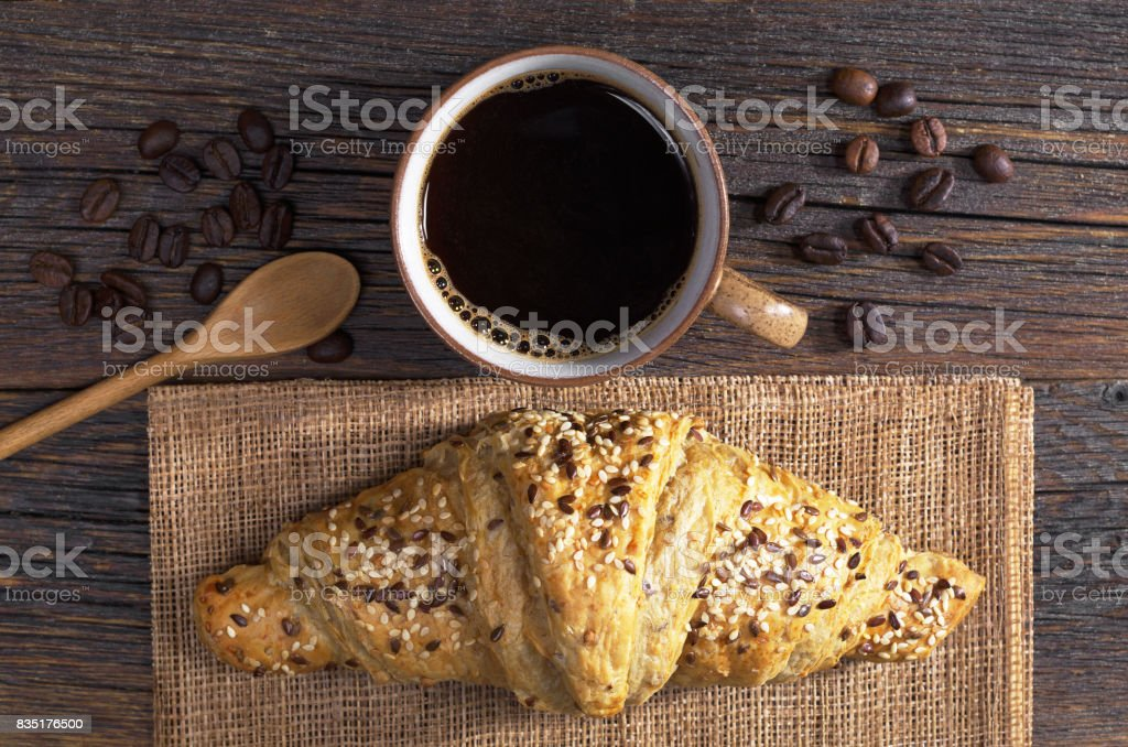 Cup of coffee and croissant with sesame seeds for breakfast on old...