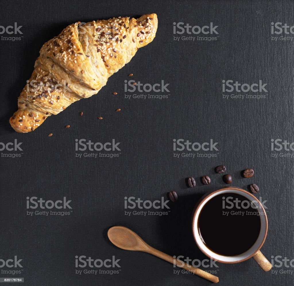 Cup of coffee and croissant with sesame seeds on black stone...