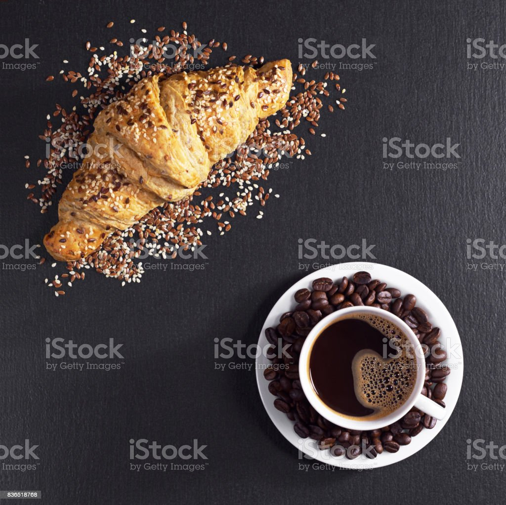 Cup of coffee and croissant with sesame seeds for breakfast on black...
