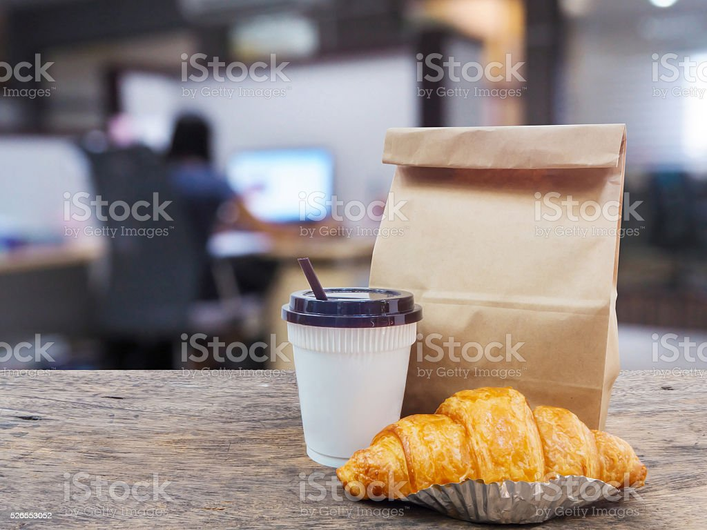 coffee and croissant with paper bag on wooden table stock photo