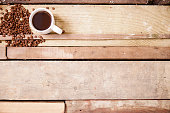 Coffee and cup with roasted beans on wooden table.