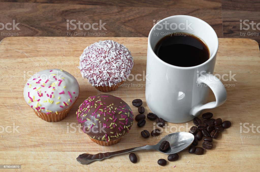 Cup of black coffee and different cupcakes on wooden board