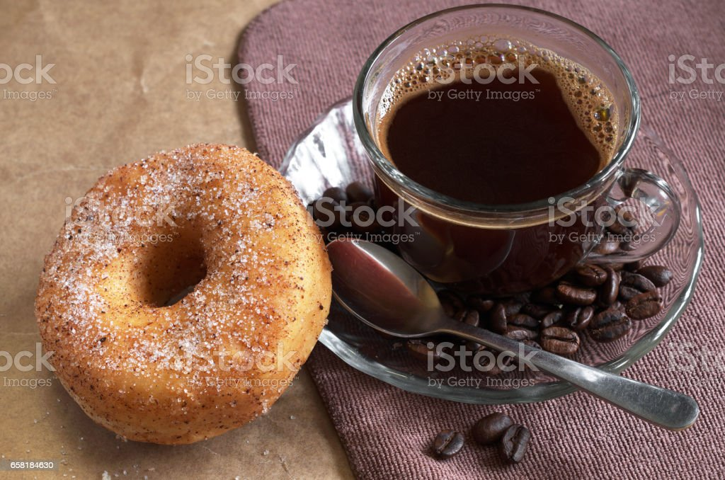 Breakfast with cup of hot coffee and donut on table