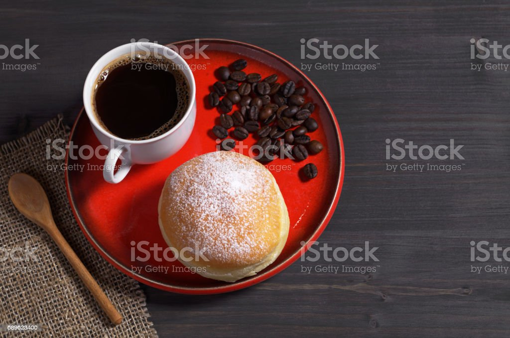 Cup of hot coffee and donut with powdered sugar in red plate on black...