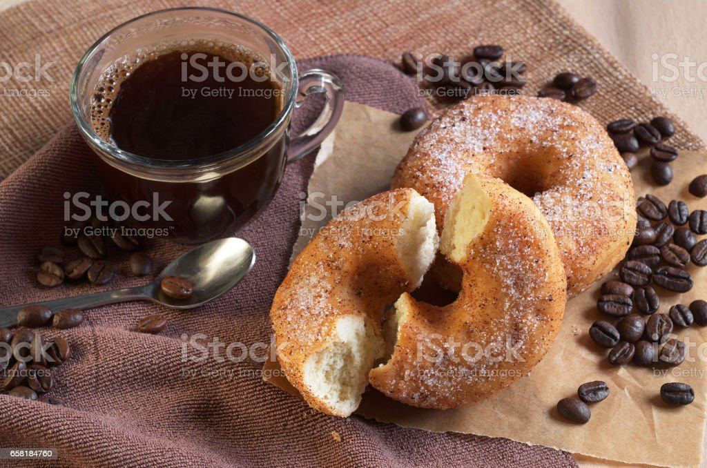 Donut with two half and cup of hot coffee for breakfast on table