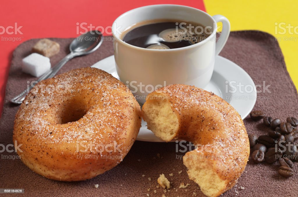 Donut and half with cup of hot coffee for breakfast on table