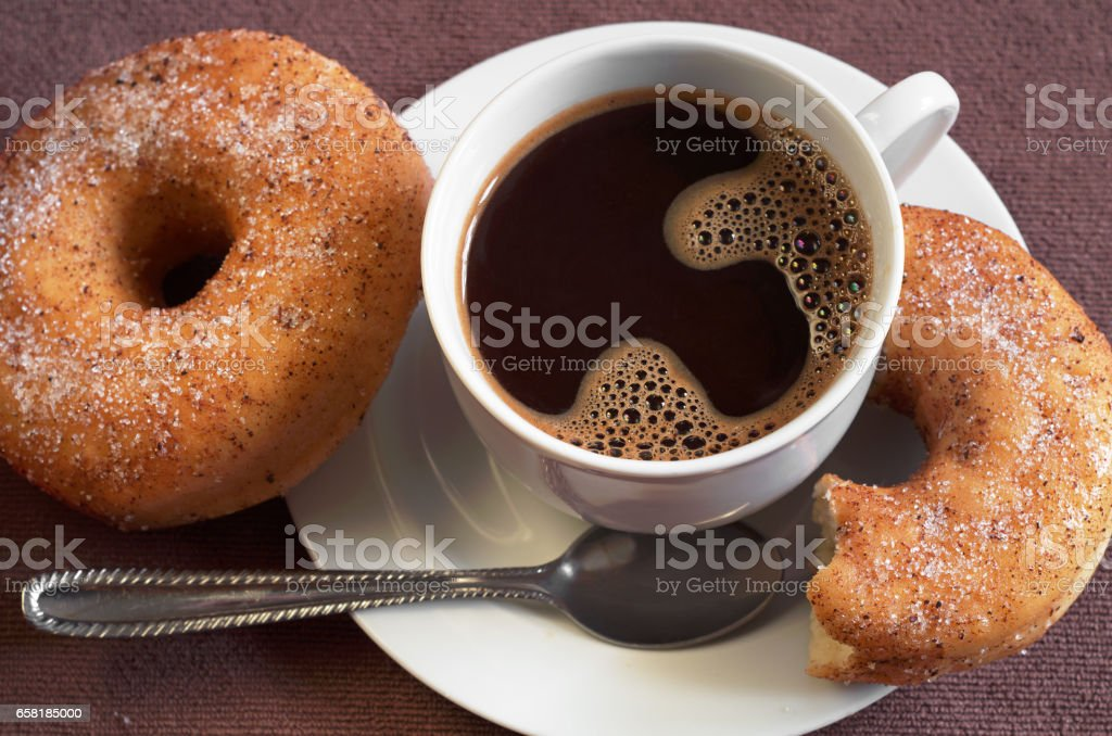 Cup of hot coffee with classic donuts on table close up. Selective...