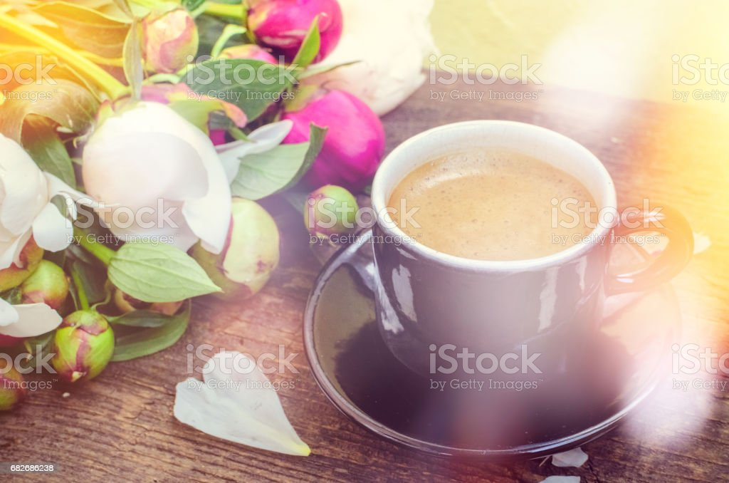 Espresso and flowers peony background. A cup of coffee and Peonies on...