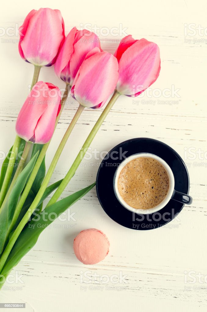 A cup of coffee, almond cookie macaroon and pink tulips on white...
