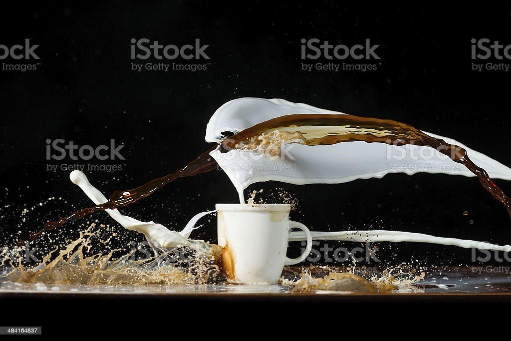 Coffee and milk pouring in a cup stock photo