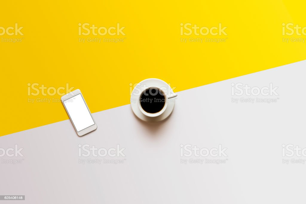 Coffee and phone on white yellow color block background stock photo