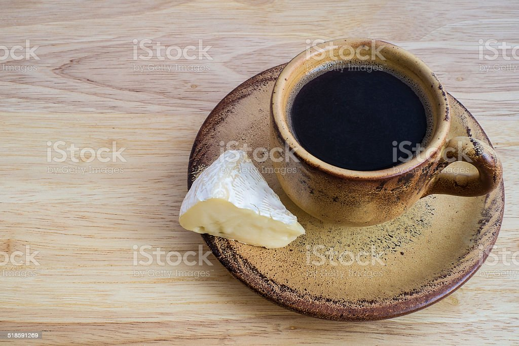 Coffee and piece of camembert cheese stock photo
