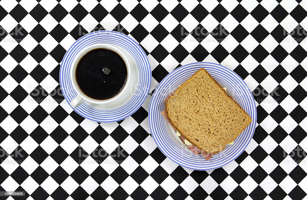 Coffee and sandwich on checkerboard tablecloth royalty-free stock photo