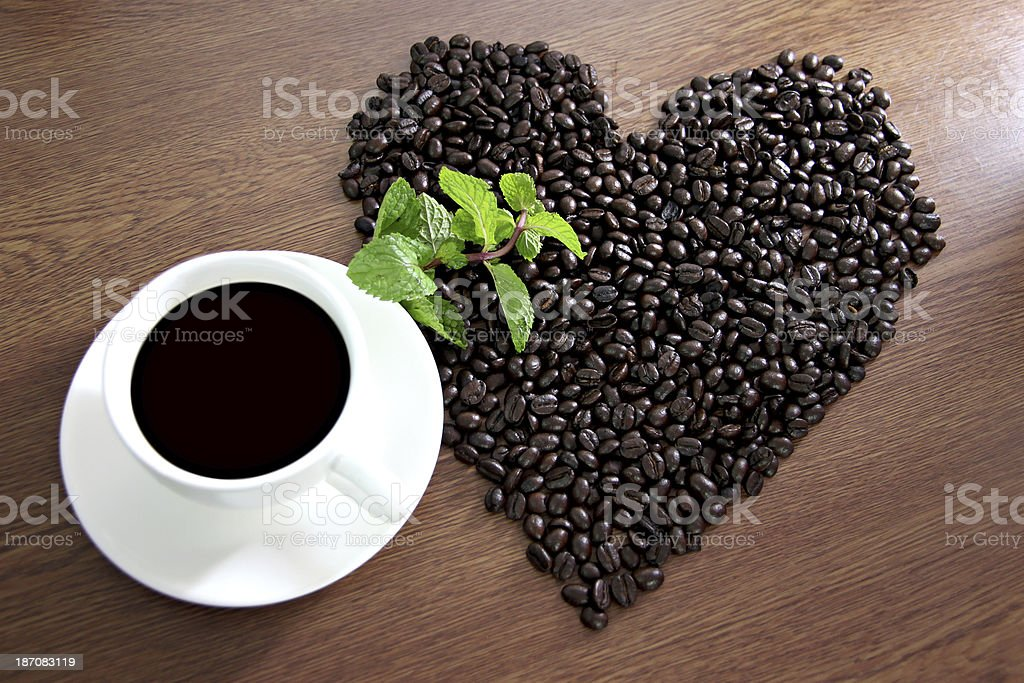 Coffee arranged in a heart shape and White Cup. royalty-free stock photo