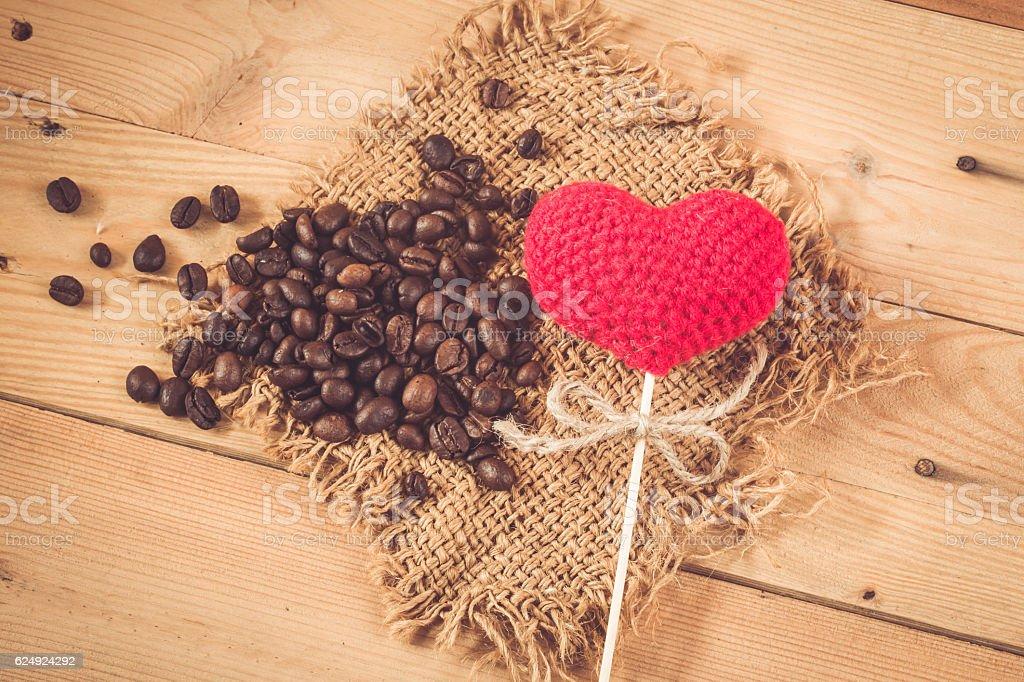 coffee bean with love heart yarn on wood sack background. stock photo