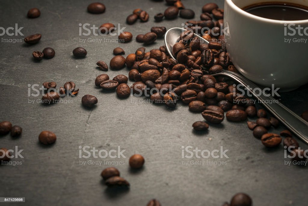 Coffee beans, a spoon and a coffee cup stock photo